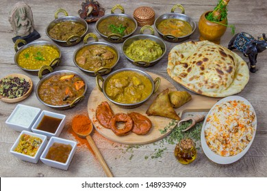 Indian food, assortment of dishes served with indian decoration in a wooden tray. Served with rice, sauce, spice and oil.