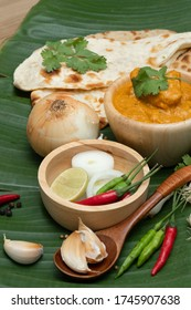 Indian food butter chicken on banana leaf background. Decorated with spice ingredient, garlic and pepper.