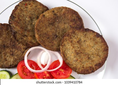 Indian food, Chapli kabab with salad, Pakistani spicy barbeque dish for ramadan iftar on white background.