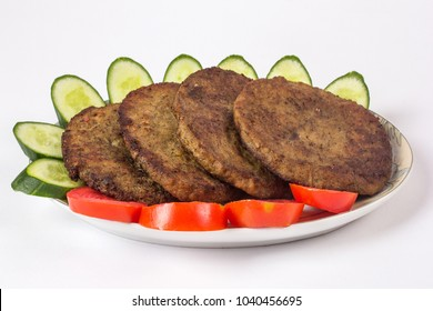 Indian food, Chapli kabab with salad, Eid party dinner, Pakistani spicy barbeque dish for ramadan iftar on white background.