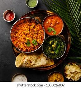 Indian food Chicken Biryani, Curry butter chicken, Palak Paneer, Papad, Dal and Naan bread on dark background