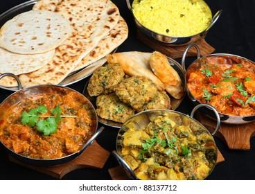Indian food with curries, rice, naan bread, samosas and pakora.