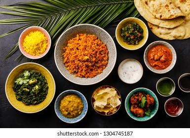 Indian food Curry butter chicken, Palak Paneer, Chiken Tikka, Biryani, Papad, Dal, Rice with Saffron and Naan bread on dark background