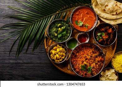 Indian food Curry butter chicken, Palak Paneer, Chiken Tikka, Biryani, Vegettable Curry, Papad, Dal, Palak Sabji, Jira Alu, Rice with Saffron on dark background
