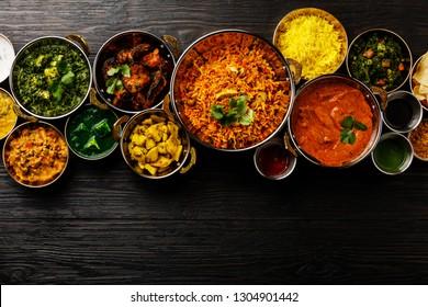 Indian food Curry butter chicken, Palak Paneer, Chiken Tikka, Biryani, Vegetable Curry, Papad, Dal, Palak Sabji, Jira Alu, Rice with Saffron on dark background copy space