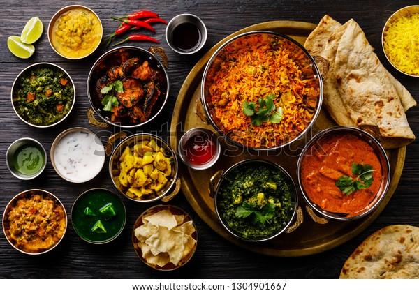 Indian food Curry butter chicken, Palak Paneer, Chiken Tikka, Biryani, Vegetable Curry, Papad, Dal, Palak Sabji, Jira Alu, Rice with Saffron on dark background