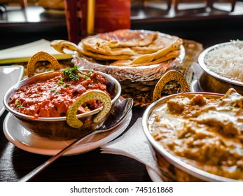 Indian Food or Indian Curry in a copper brass serving oriental bowl, pieces of chicken fillet in curry sauce ingredients in a pan with the old table side view close-up, Set of Indian food.