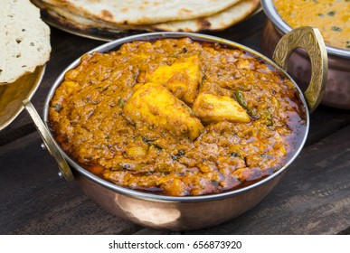 Indian Food Kadai Paneer Served With Dal Makhani, Tandoori or Papad Also Called Kadhai Paneer or Karahi Paneer is an Indian Dish of Marinated Paneer Cheese Served in Spiced Gravy on Wooden Background
