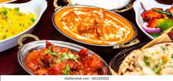 indian food on dark wooden background. Dishes and appetizers of indian cuisine. Curry, butter chicken, rice, lentils, paneer, naan, chutney, spices.