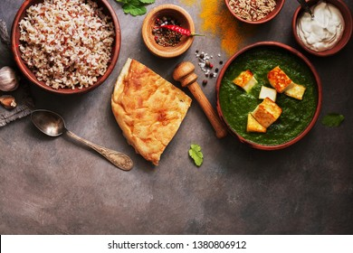 Indian food Palak Paneer , naan bread, rice and spices on a dark background. Overhead view,copy space.