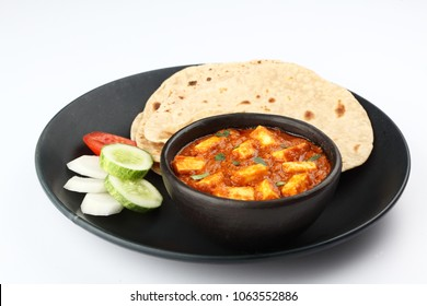 Indian food Paneer butter masala with roti served in a black ceramic plate & bowl