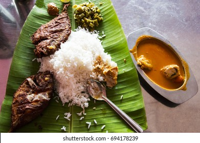the indian food with rice, fried fish and curry