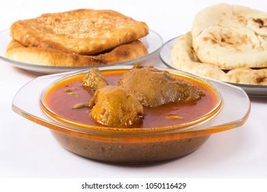 Indian food, Side view of Chicken Qorma dish with cardamom and Naan or sheermal on white background, Ramzan iftar meal, Ramadan aftari dinner.