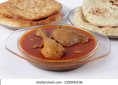Indian food, Side view of Chicken Qorma dish with cardamom and Naan or sheermal on white background, Ramzan iftar meal, Ramadan iftar dinner.