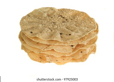 indian food stack of spiced poppadoms isolated on a white background