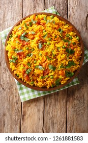 Indian food Tawa Pulao rice with vegetables and spices close-up on a plate. Vertical top view from above