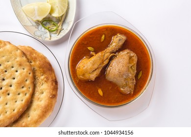 Indian food, Top view of Chicken Qorma dish with lemon and sheermal on white background, Ramzan iftar meal.