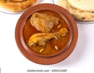Indian food, Top view of Chicken Qorma dish with cardamom and Naan or sheermal on white background, Ramzan iftar meal, Ramadan aftari dinner.