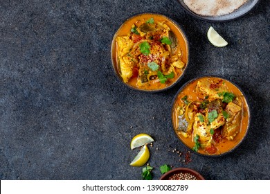 INDIAN FOOD. Traditional KERALA FISH CURRY with naan bread, gray plate, black background.