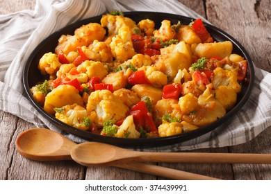 Indian food: vegetarian Gobi Aloo close-up on the table. horizontal, rustic