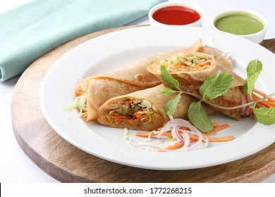 Indian Frankie Veg chapati Wrap / Kathi Roll, served in a plate with sauce & mint chutney. selective focus