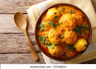 Indian fried potatoes Dum aloo in curry sauce close-up in a bowl. horizontal top view from above