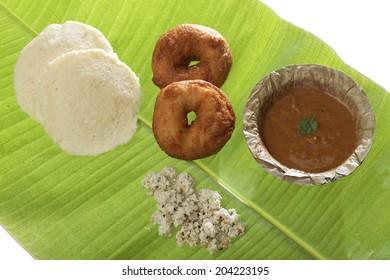 Indian fried snack medu vada & idli on a banana leaf with coconut chutney and sambhar.