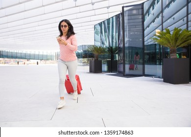 Indian girl carrying wheeled luggage and running to airport. Serious young woman using phone on move. She being late to airplane. Be in hurry concept