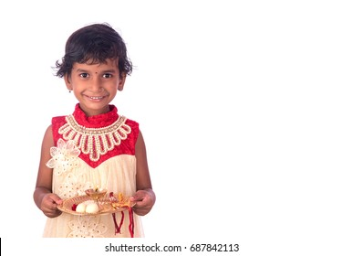 Indian girl child performing worship, portrait of a beautiful young girl child with pooja thali isolated on white background