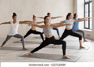 Indian girl and diverse group of young sporty people practicing yoga, doing Warrior II exercise, Virabhadrasana 2 pose, working out, indoor full length, female students training at sport club, studio