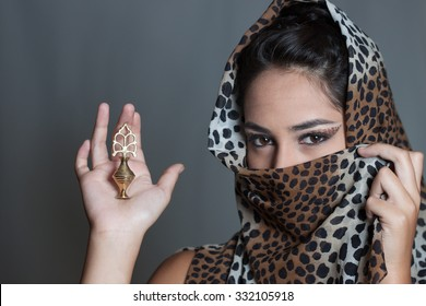 Indian girl face covered leopard spotted veil holding kajal pot