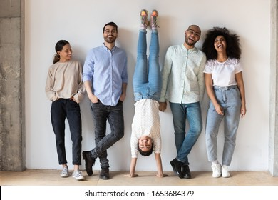 Indian girl fools around standing on hands upside-down having fun during photo shooting with multi-ethnic friends. Full length five cheery buddies laughing photographing posing near grey wall indoors
