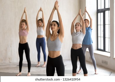 Indian girl and a group of young sporty people doing yoga mountain exercise, Tadasana pose, working out indoor, active female students training at sport club or studio. Well being, wellness concept