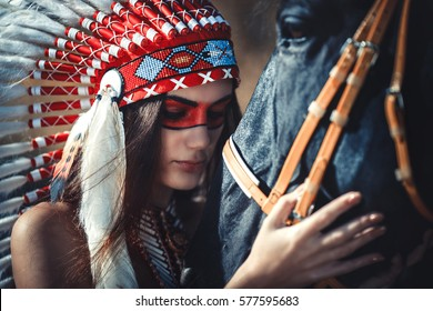 Indian girl and horse looking into each other's eyes.