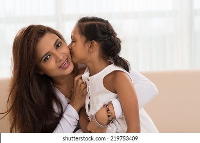 Indian girl kissing her mother indoors