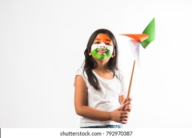indian girl with paper windmill toy made up of tricolour and face painted with indian flag colours.Suitable for Happy Independence day or Republic day greeting.