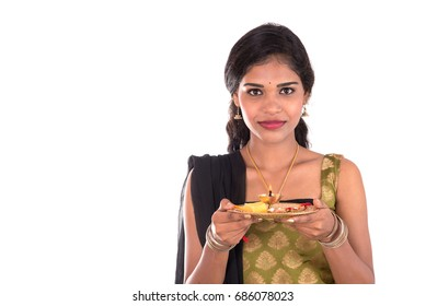 Indian Girl performing worship, portrait of a beautiful young lady with pooja thali isolated on white background.