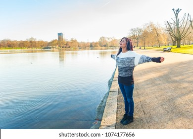 Indian girl relaxing at park in London on a sunny spring day. Young woman next to a lake with trees on background. Lifestyle and travel concepts with candid real person.