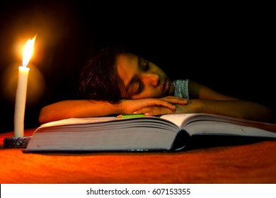 An Indian girl sleeping on a book - no electricity, blackout ,