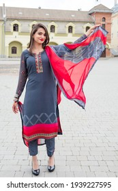 An Indian girl stands on the street of the city. Girl in traditional Indian clothing, salwar kameez.