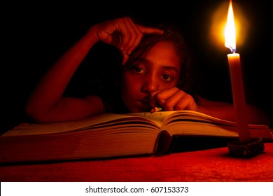 An Indian girl studying in candle light, no electricity, blackout