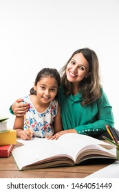 Indian girl studying with mother or teacher at study table with laptop computer, books and having fun learning