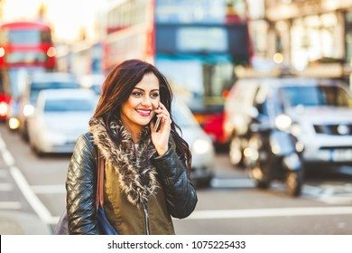 Indian girl talking on the phone in London. Young woman standing by a busy road with blurred traffic on background and having a conversation using her smartphone. Travel and lifestyle concepts