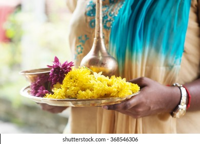 Indian girl with traditional plate of religious offerings and flowers for ear piercing ceremony.