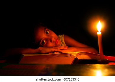 An Indian girl trying to study in candle light, Electricity,