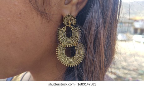 Indian gold jewellery exhibition on girl ear.