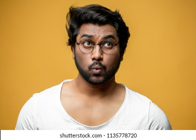 Indian good-looking man with funny facial expression trying to whistle. ignore people