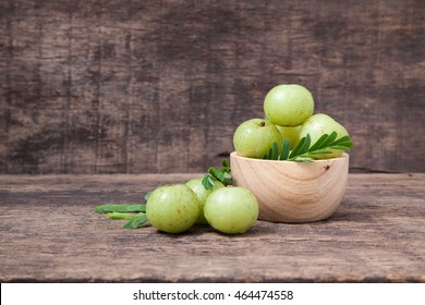Indian gooseberry or amla fruit with leaf in wooden bowl isolated on wooden background