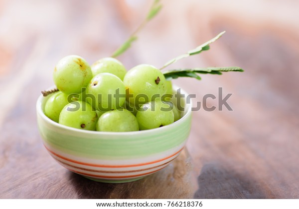 Indian gooseberry fruit in a bowl on wooden background.Healthy and highest vitamin C fruit