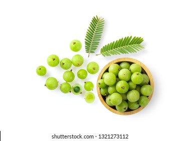 Indian gooseberry and leaf in wood bowl on white background. top view